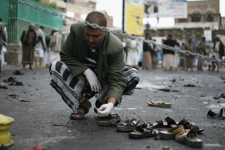 A Yemeni security official inspects the site of a suicide bombing in Sanaa, Yemen, Thursday, Oct. 9, 2014. A suicide bomber struck at the center of the Yemeni capital of Sanaa on Thursday, setting off his explosives at a gathering of supporters of the rebel Shiite Houthis who recently overran the city, security officials said. Photo: Uncredited / Associated Press / AP