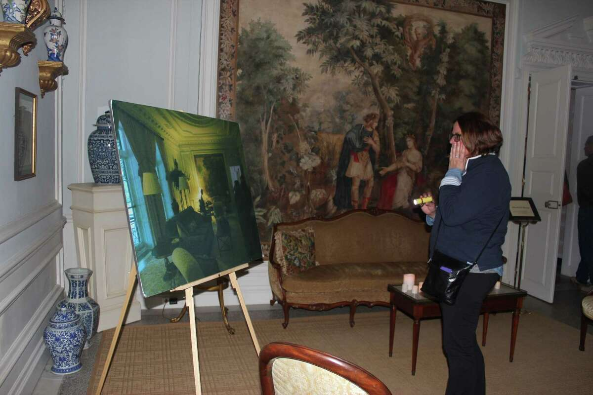 A visitor looks at a photo in the Edith Wharton estate during the ghost tour. The photo has a mysterious shadow image of a woman with an elongated neck. (Donna Liquori)
