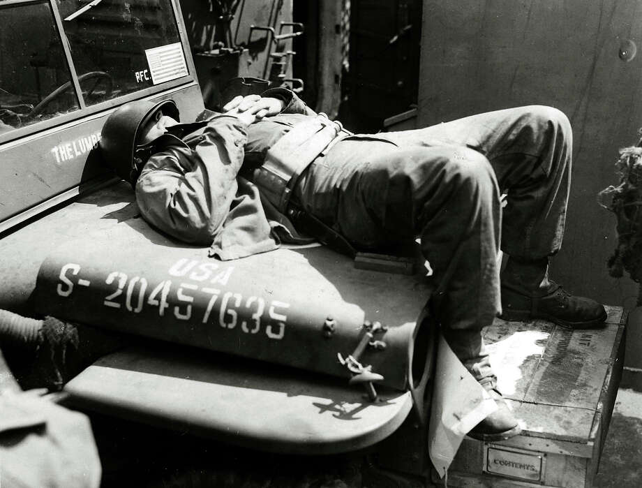 An American soldier fast asleep on the hood of his jeep, as the troopship nears the Normandy coast of France in 1944. Photo: Popperfoto, Getty Images / Popperfoto