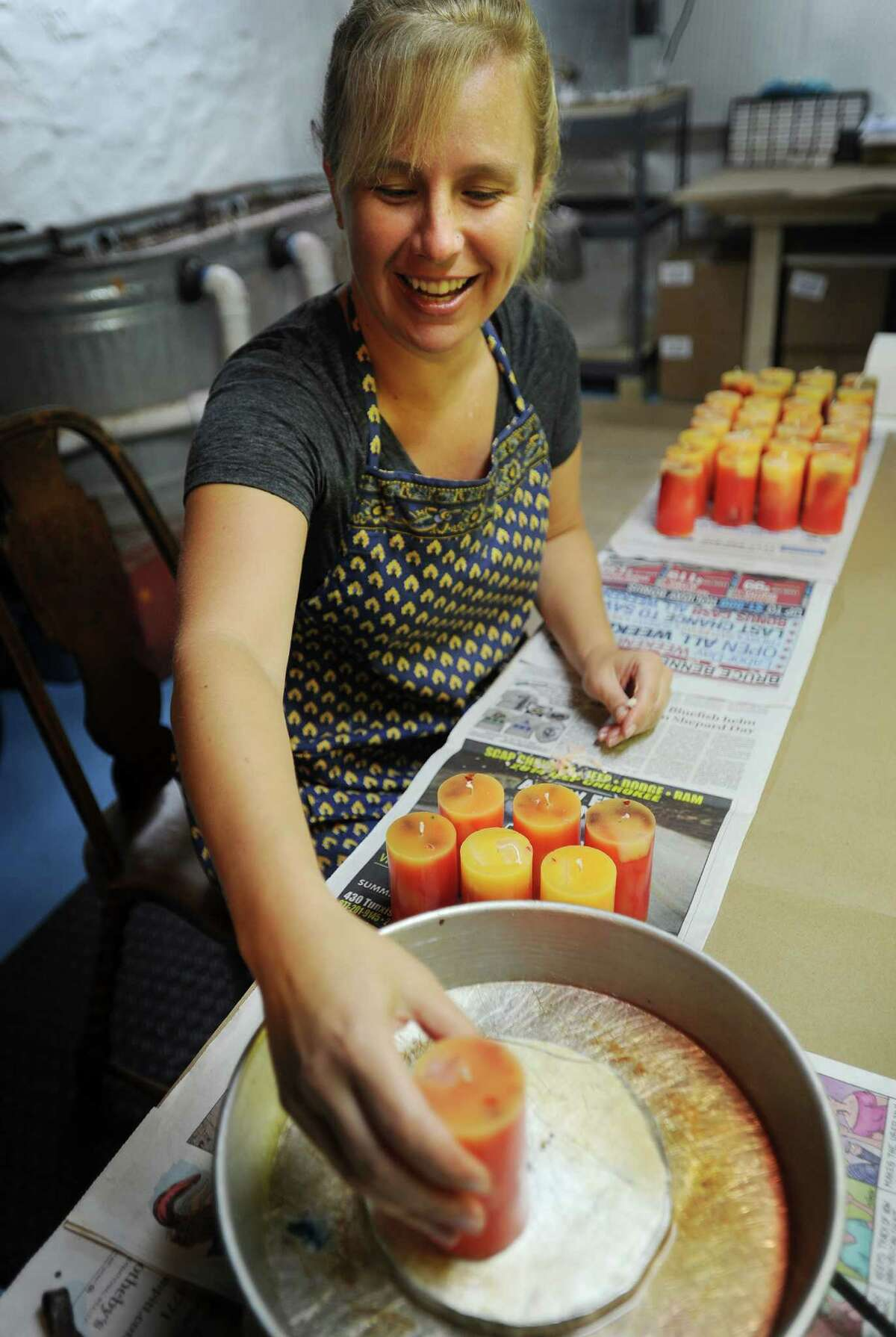 Jenn Heatly, owner of Zena Moon, melts smooth the bottoms on a batch of scented candles, the final step in her manufacturing process, in the basement of her Norwalk home on Thursday, October 9, 2014.