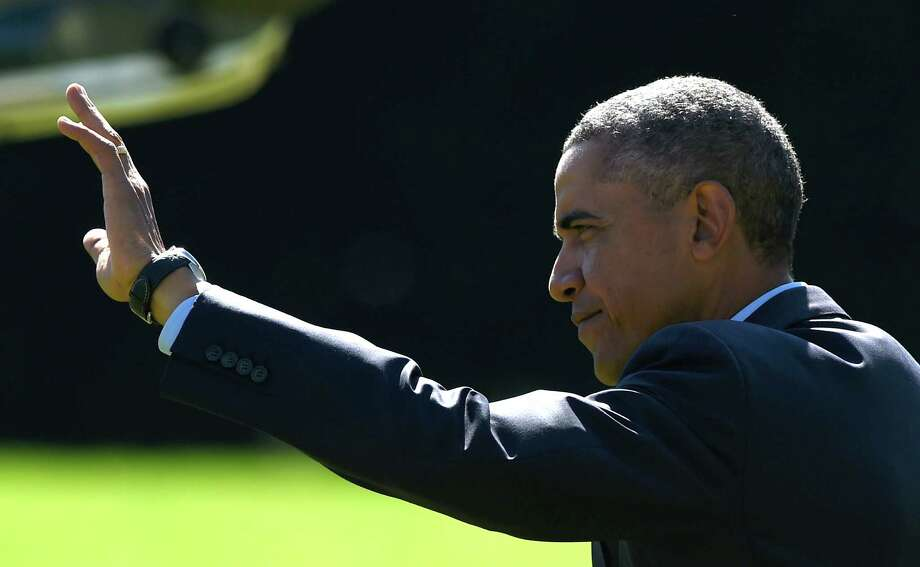 President Barack Obama waves as he walks to Marine One on the South Lawn of the White House in Washington, Thursday, Oct. 9, 2014, for a short trip to Andrews Air Force Base, Md., then onto California for three days. (AP Photo/Susan Walsh) Photo: Susan Walsh / Associated Press / AP