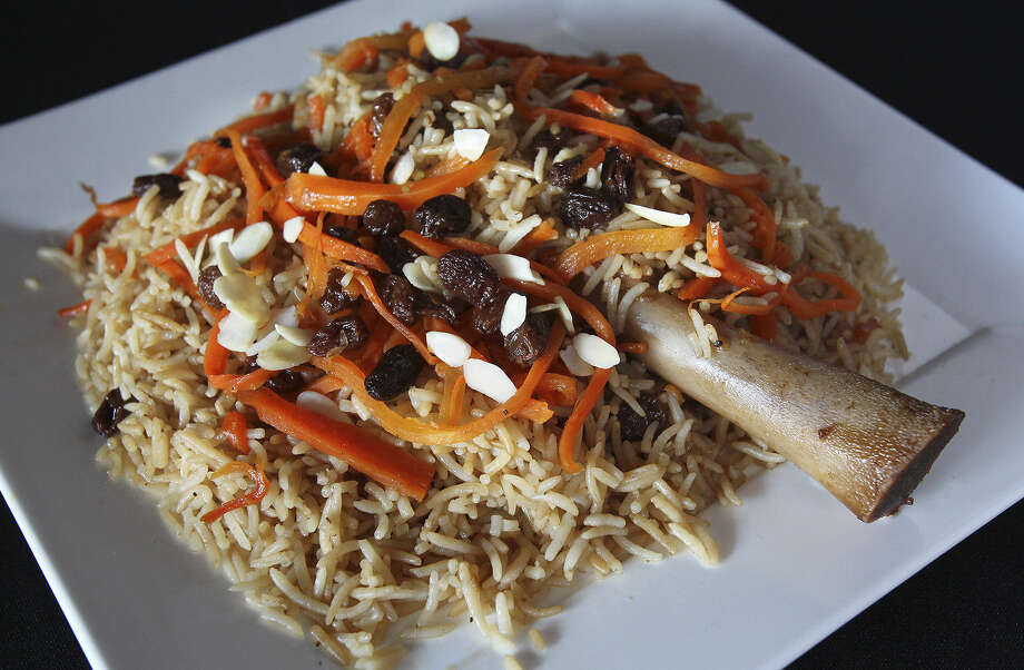Kabuli Palow, a tender braised lamb shank covered with a mound of basmati rice topped with carrots, raisins and nuts, is a treasured Afghan dish. Photo: Photos By Tom Reel / San Antonio Express-News