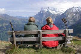 A well-situated bench rewards these hikers with a spectacular alpine panorama.