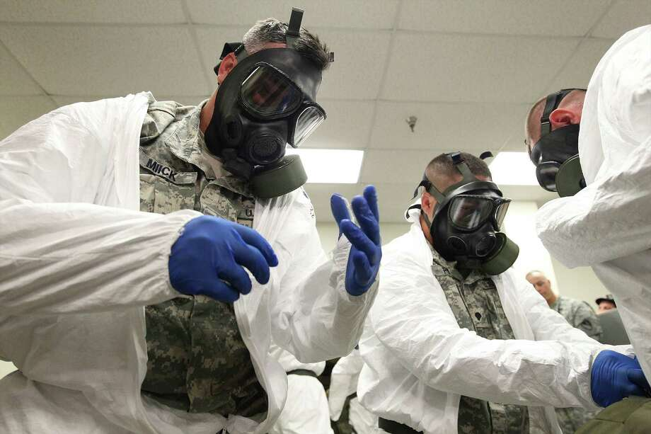 At Fort Hood, soldiers headed for Liberia practice donning protective gear. Photo: Kin Man Hui, MBO / San Antonio Express-News
