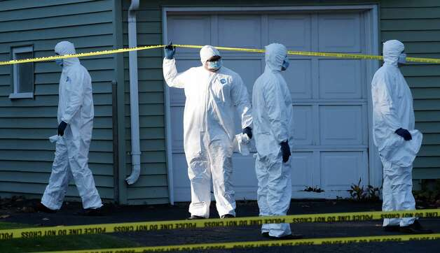 Albany County District Attorney David Soares holds the crime scene tape for his team members at the scene of a quadruple homicide at 1846 Western Avenue early Thursday morning Oct. 9, 2014 in Guilderland, N.Y.     (Skip Dickstein/Times Union) Photo: SKIP DICKSTEIN / 10028967A
