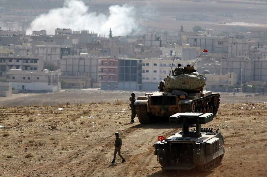 Turkish soldiers, with a tank and an armored vehicle, occupy a border hilltop  overlooking  Kobani, Syria. Photo: Lefteris Pitarakis / Associated Press / AP