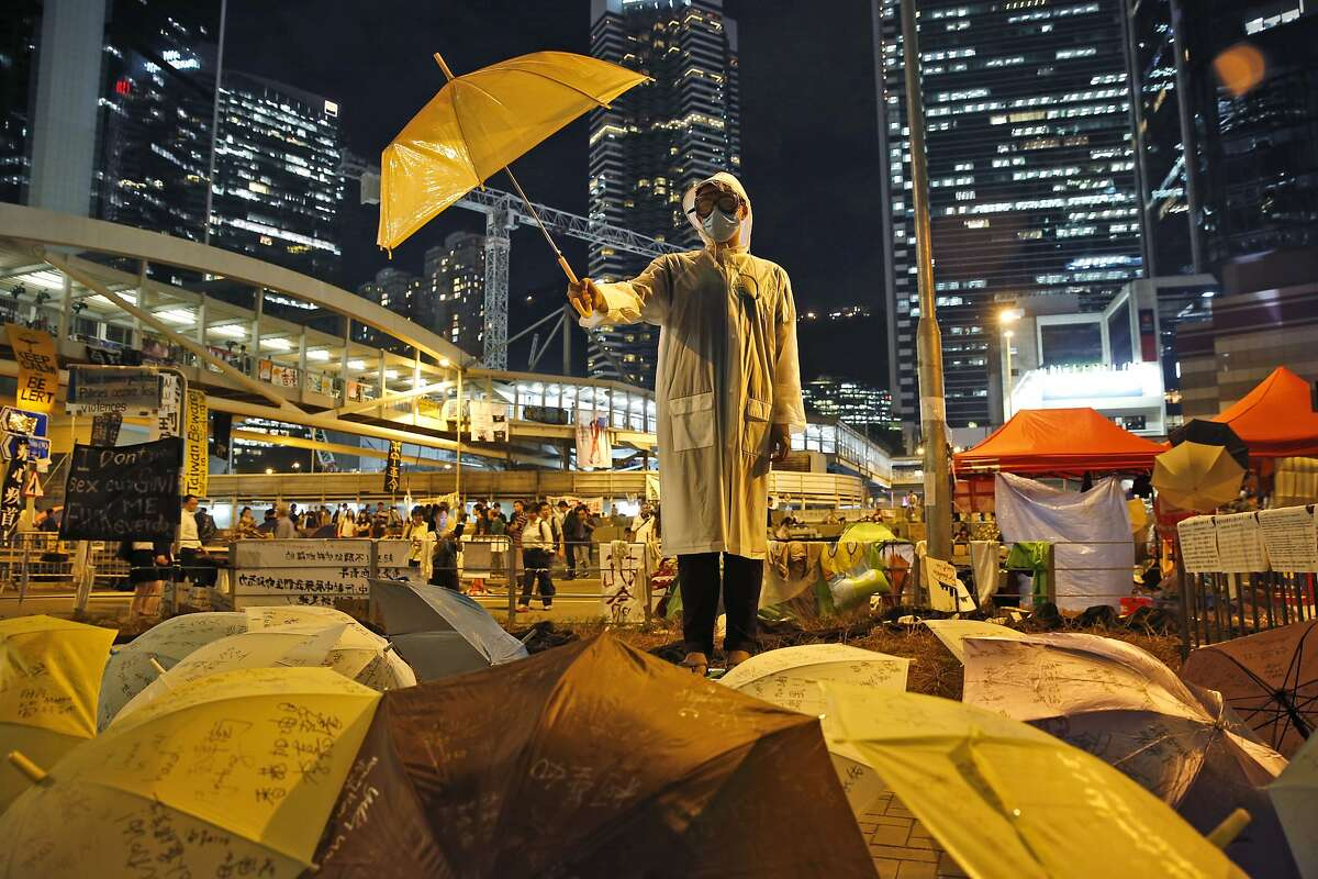 A protester holds an umbrella during a performance on a main road in the occupied areas outside government headquarters in Hong Kong's Admiralty in Hong Kong Thursday, Oct. 9, 2014. Talks between the Hong Kong government and student leaders of a democracy protest that has blocked main roads in the Asian financial hub for nearly two weeks are canceled because they're unlikely to be constructive, a senior government official said Thursday. (AP Photo/Kin Cheung)