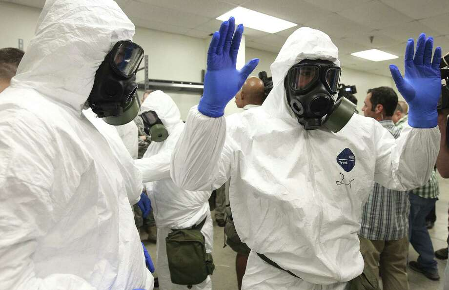 Soldiers from the 36th Engineer Brigade at Fort Hood train to put on protective clothing and gloves. The brigade is set to deploy to Liberia, where it will be building medical facilities. Photo: Kin Man Hui / San Antonio Express-News / ©2014 San Antonio Express-News