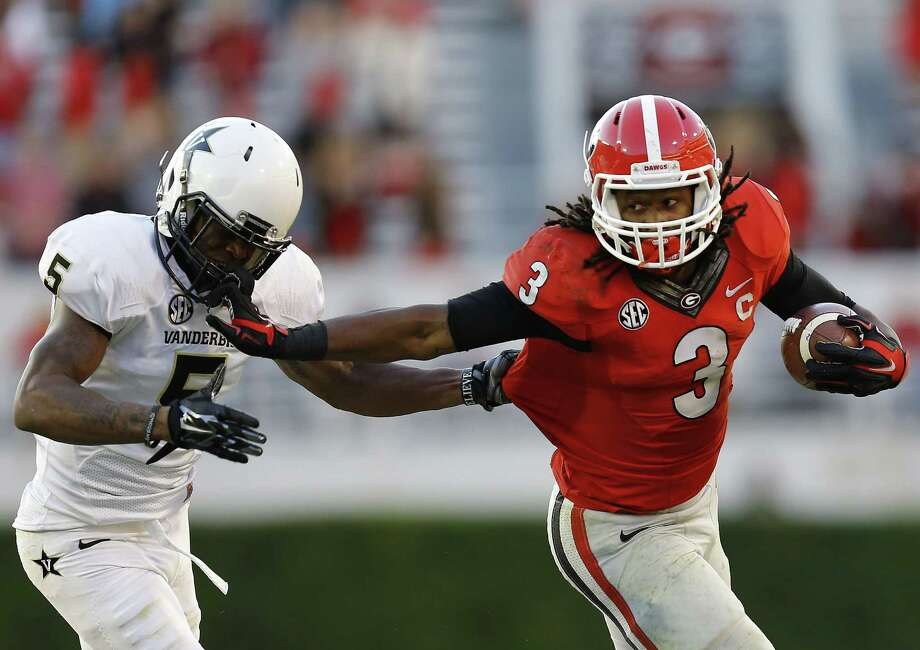 ATHENS, GA - OCTOBER 04:  Running back Todd Gurley #3 of the Georgia Bulldogs stiff arms cornerback Torren McGaster #5 of the Vanderbilt Commodores during a running playin the game at Sanford Stadium on October 4, 2014 in Athens, Georgia.  (Photo by Mike Zarrilli/Getty Images) Photo: Mike Zarrilli / Getty Images / 2014 Getty Images