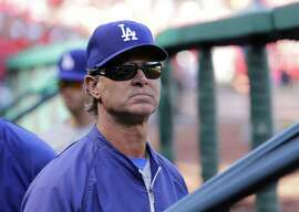 Los Angeles Dodgers manager Don Mattingly stands in the dugout before Game 4 of baseball's NL Division Series against the St. Louis Cardinals, Tuesday, Oct. 7, 2014, in St. Louis. (AP Photo/Charles Rex Arbogast)