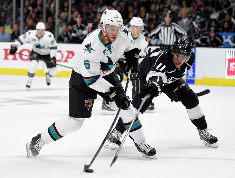 San Jose Sharks defenseman Jason Demers, left, shoots the puck as Los Angeles Kings center Anze Kopitar, of Slovenia, defends during the first period of an NHL hockey game, Wednesday, Oct. 8, 2014, in Los Angeles. (AP Photo/Mark J. Terrill) Photo: Mark J. Terrill / Associated Press / AP