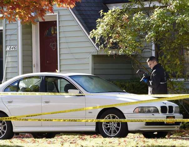 A State Police forensics investigator photographs a car Friday in front of 1846 Western Ave., Guilderland, the home where two adults and two children were found dead on Wednesday. (Skip Dickstein / Times Union)