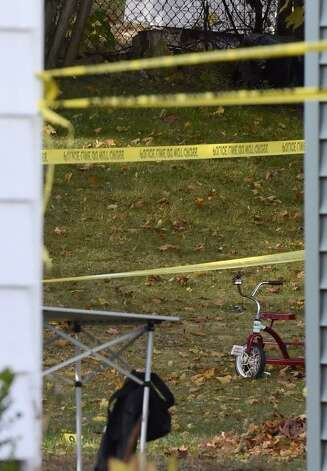 A child's tricycle sits behind 1846 Western Ave., Guilderland, the home where two adults and two children were found dead on Wednesday. (Skip Dickstein / Times Union)