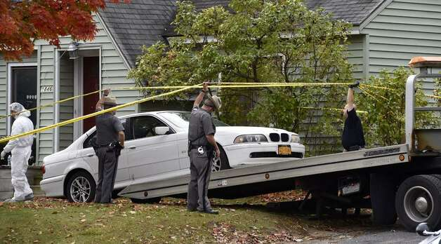 A State Police prepare to tow away car Friday that was left in front of 1846 Western Ave., Guilderland, the home where two adults and two children were found dead on Wednesday. (Skip Dickstein / Times Union)