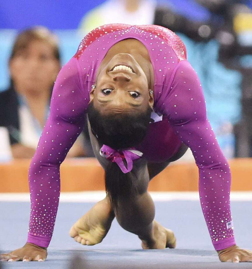 Simone Biles of the US performs on the floor during the women's all-around final at the gymnastics world championships in Nanning on October 10, 2014.   AFP PHOTO/KAZUHIRO NOGIKAZUHIRO NOGI/AFP/Getty Images Photo: KAZUHIRO NOGI, AFP/Getty Images / AFP