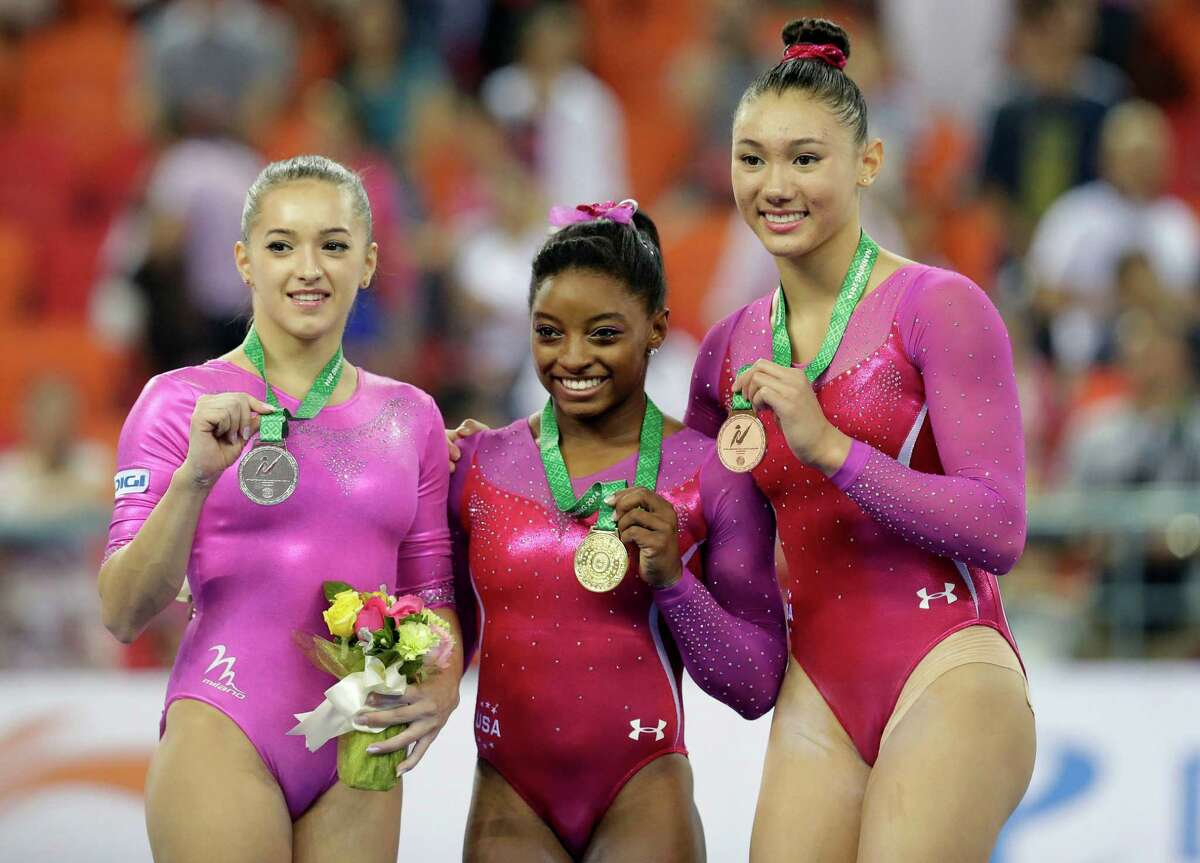 Gold medalist Simone Biles of the U.S, center, second place Larisa Andreea Iordache of Romania, left, and third place Kyla Ross of the U.S pose on podium after the awards ceremony of the women's all-round final of the Artistic Gymnastics World Championship at the Guangxi Gymnasium in Nanning, capital of southwest China's Guangxi Zhuang Autonomous Region Friday, Oct. 10, 2014. (AP Photo/Andy Wong)