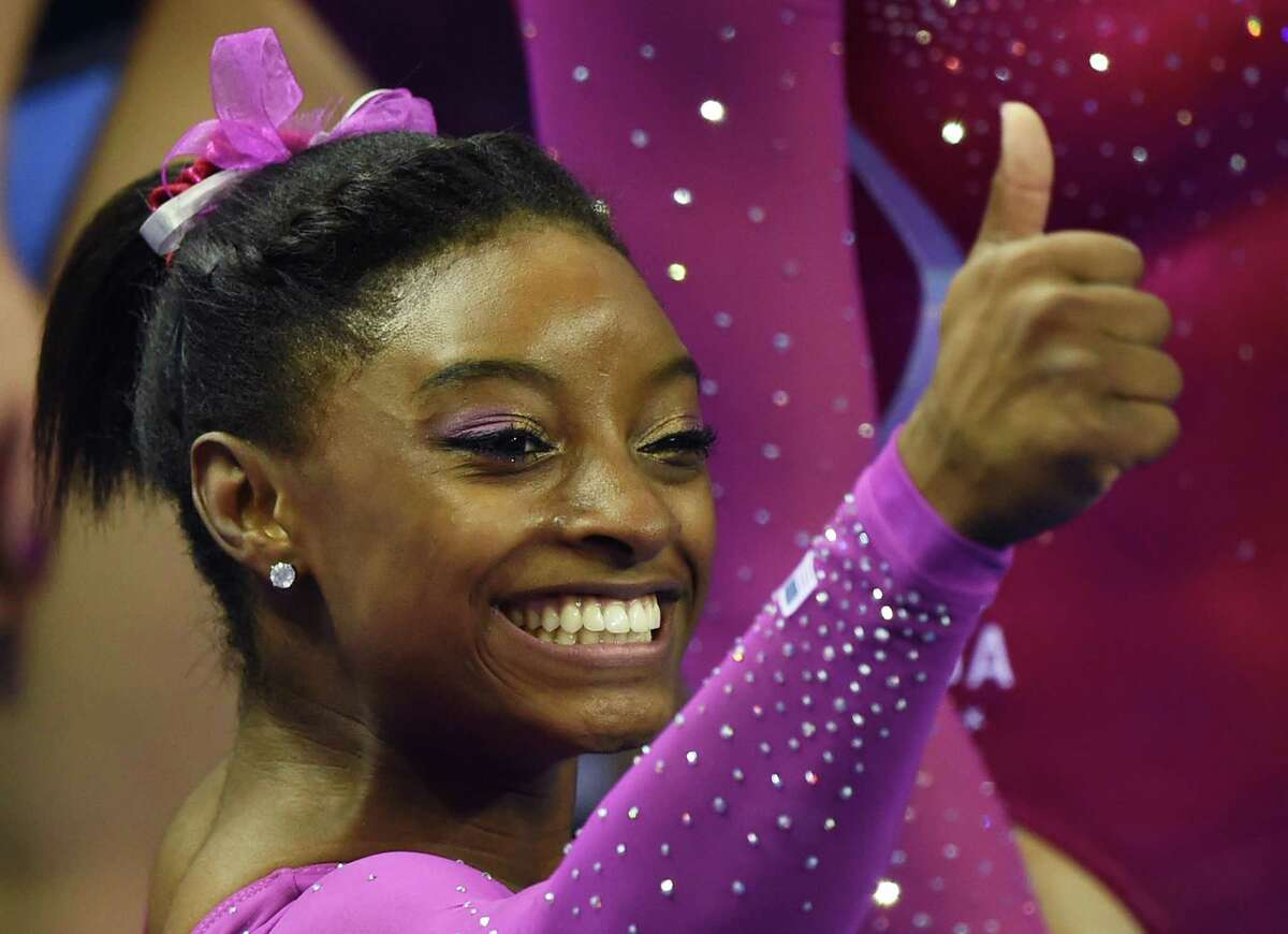 Simone Biles of the US gives the thumbs up to supporters after winning the women's all-around final at the Gymnastics World Championships in Nanning, in China's southern Guangxi province on October 10, 2014. AFP PHOTO/Greg BAKERGREG BAKER/AFP/Getty Images