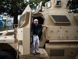 Return to sender: Lt. Thomas Waltz climbs down from an armored vehicle that showed up, unwelcomed, in Davis.