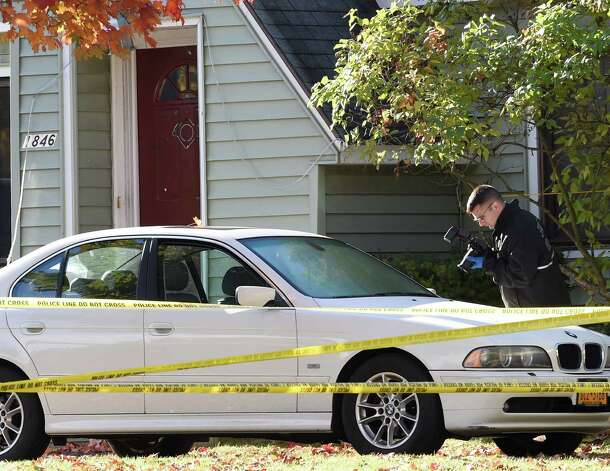 A New York State Police forensics investigator makes a photograph of some detail on a car that was parked in front  of the scene of a quadruple homicide at 1846 Western Avenue Friday morning, Oct. 10, 2014, in Guilderland, N.Y.    (Skip Dickstein/Times Union) Photo: SKIP DICKSTEIN