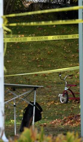 A tricycle sits idle in the rear of the building which was the scene of Wednesday's quadruple homicide at 1846 Western Avenue Friday morning, Oct. 10, 2014,  in Guilderland, N.Y. (Skip Dickstein/Times Union) Photo: SKIP DICKSTEIN