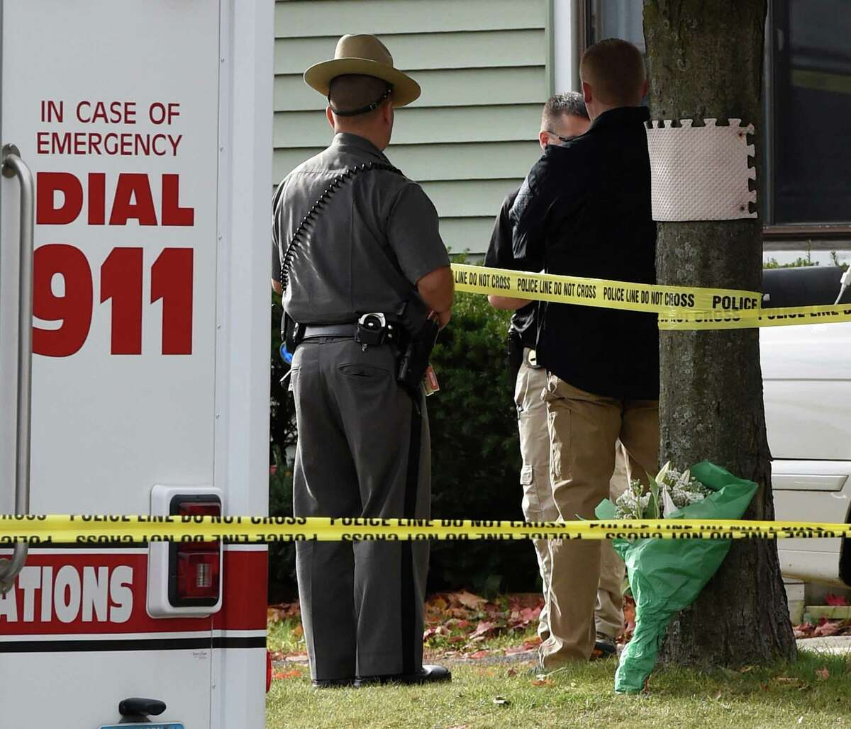 A bouquet of flowers is seen by a tree in front at the crime scene as New York State Police forensics unit members return to continue the investigation of a quadruple homicide at 1846 Western Avenue Friday morning, Oct. 10, 2014, in Guilderland, N.Y. (Skip Dickstein/Times Union)