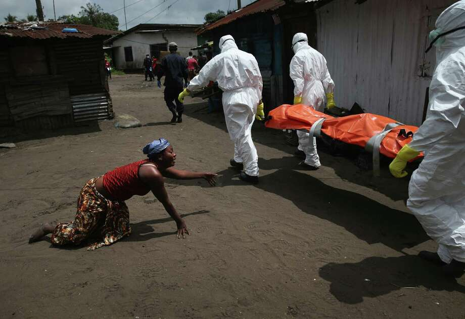 A woman crawls towards the body of her sister as Ebola burial team members take her sister Mekie Nagbe, 28, for cremation on October 10, 2014 in Monrovia, Liberia. Nagbe, a market vendor, collapsed and died outside her home earlier in the morning while leaving to walk to a treatment center, according to her relatives. The burial of loved ones is important in Liberian culture, making the removal of infected bodies for cremation all the more traumatic for surviving family members. The World Health Organization says the Ebola epidemic has now killed more than 4,000 people in West Africa. Photo: John Moore / Getty Images / 2014 Getty Images