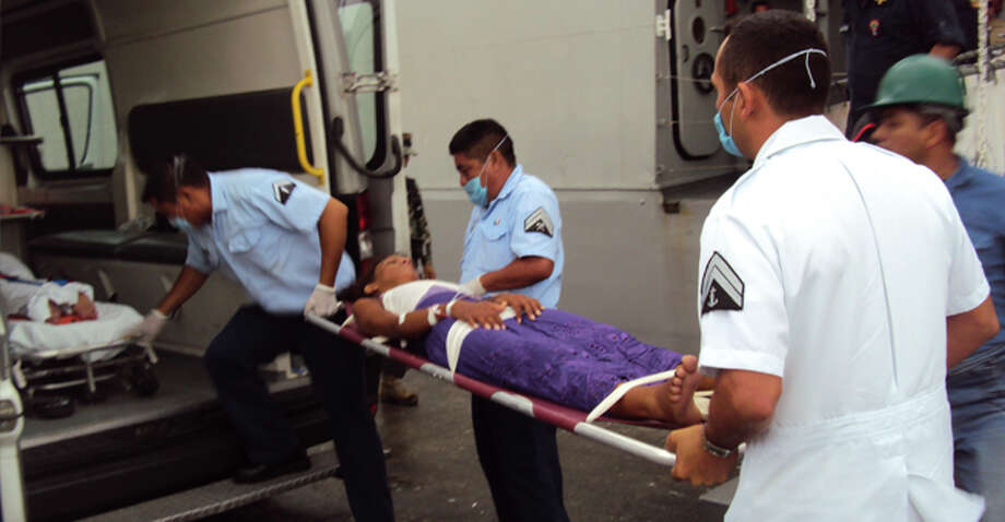In this photo released by Mexico's Secretaria de Marina (SEMAR) on Sept. 1, 2014, Mexican sailors transport a Cuban woman who was rescued with 14 others on a makeshift raft off the coast of Mexico nearest to Puerto Progreso, Yucatan state after it was intercepted by Mexican sailors. It was one of the worst Cuban rafter tragedies in recent years. Thirty-two migrants had set sail this summer from Manzanillo, on the island's southern edge, and got lost at sea for nearly a month. When Mexican fishermen came across the raft, only 15 people were still alive. The others had died at sea, their bodies thrown overboard, or tried to swim ashore. Two of the survivors later died. Photo: Associated Press / semar