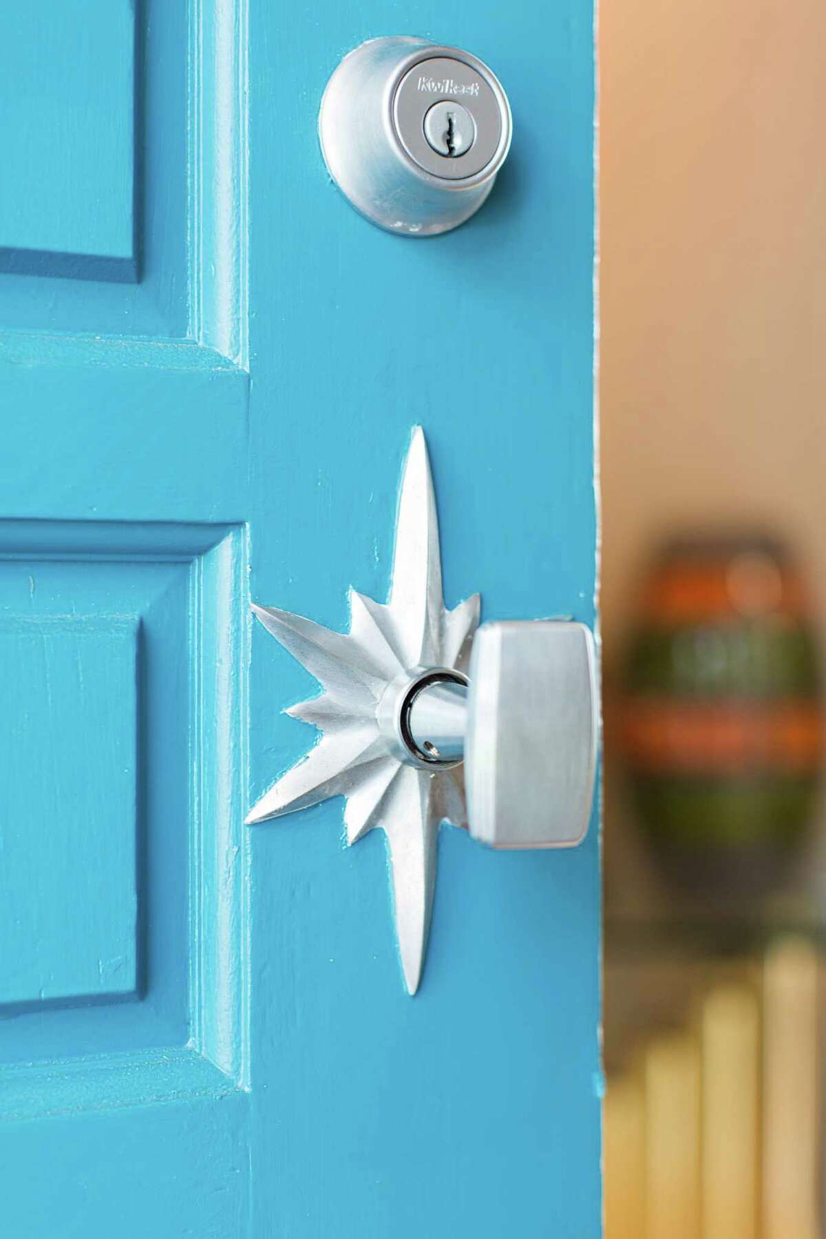 Dave Seeburger of P&G Homes and designer Jamie House restored the original front door and painted it a vibrant turquoise. The starburst blackplate was found on eBay.