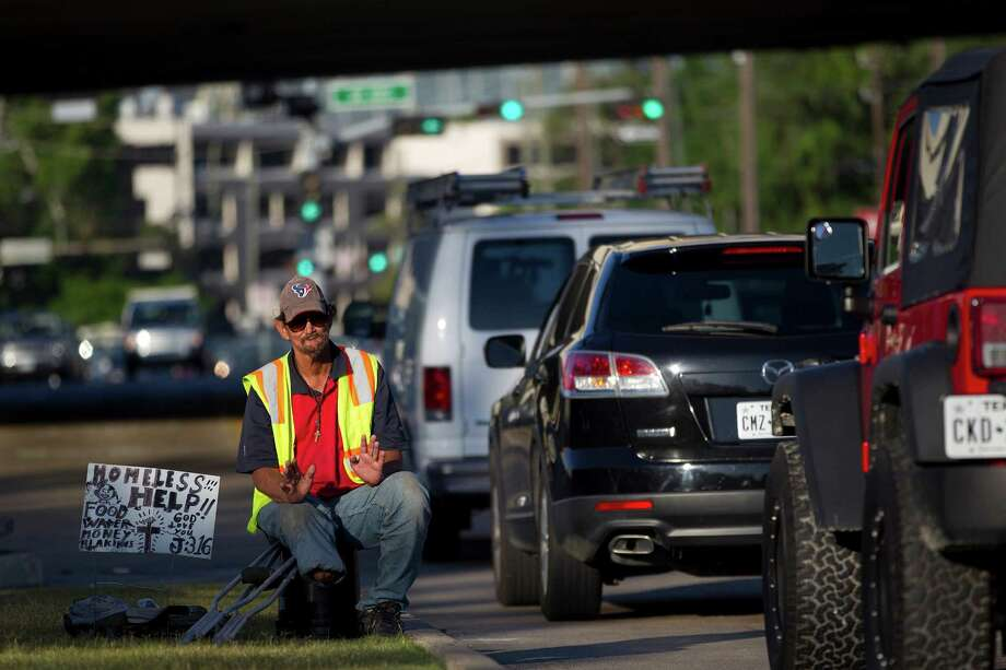 """This is what I do,"" Paul Carbonneau, 59,  said as he gave a little wave to the cars passing by as he panhandled on Woodway Drive at the West 610 Loop  in May. Making only $15, Paul said he'd had a bad morning. Photo: Johnny Hanson / © 2014  Houston Chronicle"