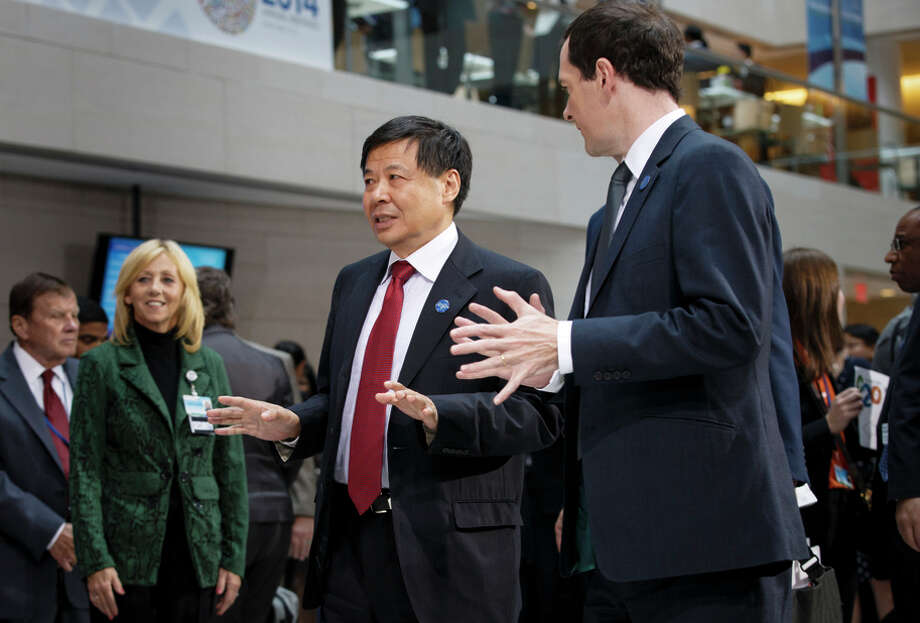 China's Vice Finance Minister Zhu Guangyao walks with Chancellor of the Exchequer George Osborne (right) in 2014. Photo: J. Scott Applewhite / Associated Press / AP