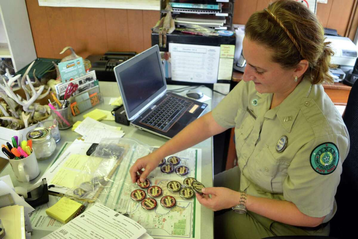 Sorting through Junior Ranger badges, Interpretive Ranger Cara Bierschwale is helping families visiting Garner State Park learn about the facility's plants, animals and history.