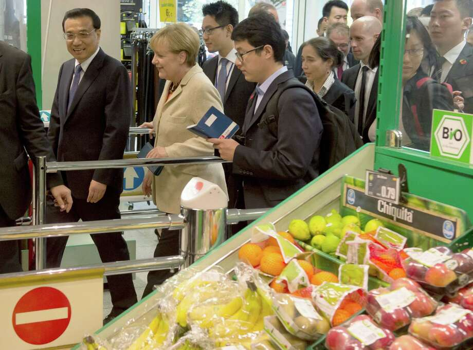 German Chancellor Angela Merkel, center, and Chinese Prime Minister Li Keqiang, left, walk through the vegetable section of a supermarket between two events of the German-Chinese government consultations in Berlin, Friday,  Oct. 10, 2014. (AP Photo/dpa, Tim Brakemeier) ORG XMIT: FOS115 Photo: Tim Brakemeier / dpa