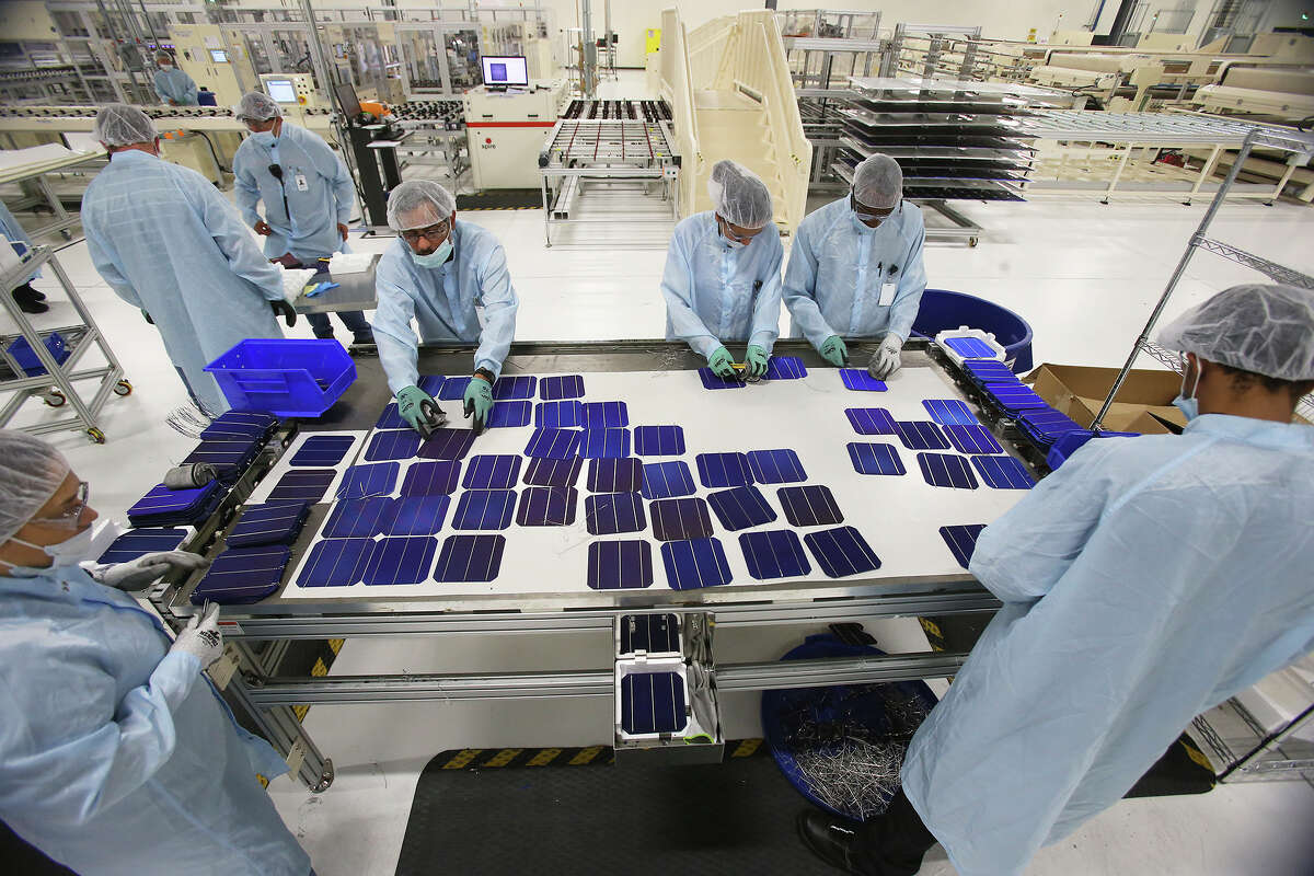 Employees gather to reconstruct a panel as Mission Solar produces solar panels at its Brooks City Base location. The operation is emblamatic of manufacturing's importantce to San Antonio.