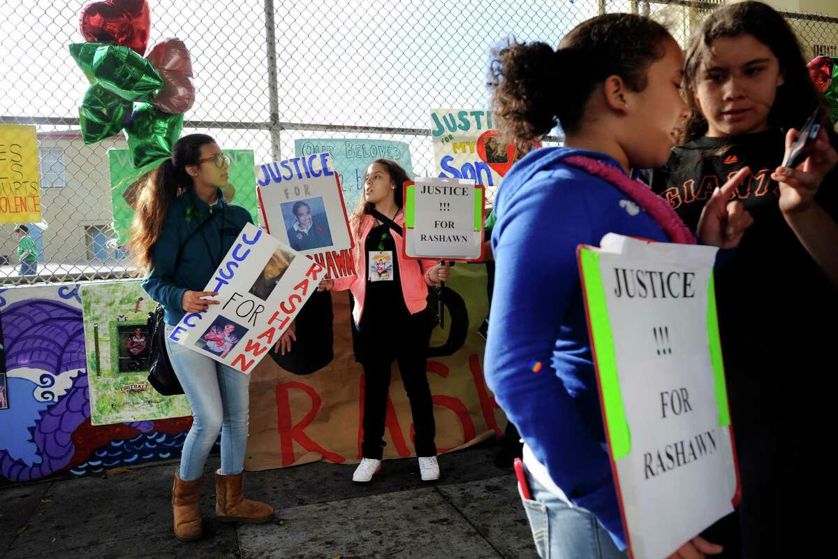 Ariana Cordova, left, and Adriana Estevez hold signs with others during a demonstration for Rashawn Williams, a 14-year-old student killed by a classmate, at Buena Vista Horace Mann Elementary School in San Francisco, CA, October 10, 2014. The family of Rashawn Williams, a 14-year-old honor roll student and football star who was killed by a classmate, is calling for the San Francisco district attorney to charge the 14-year-old boy accused of killing Rashawn as an adult.