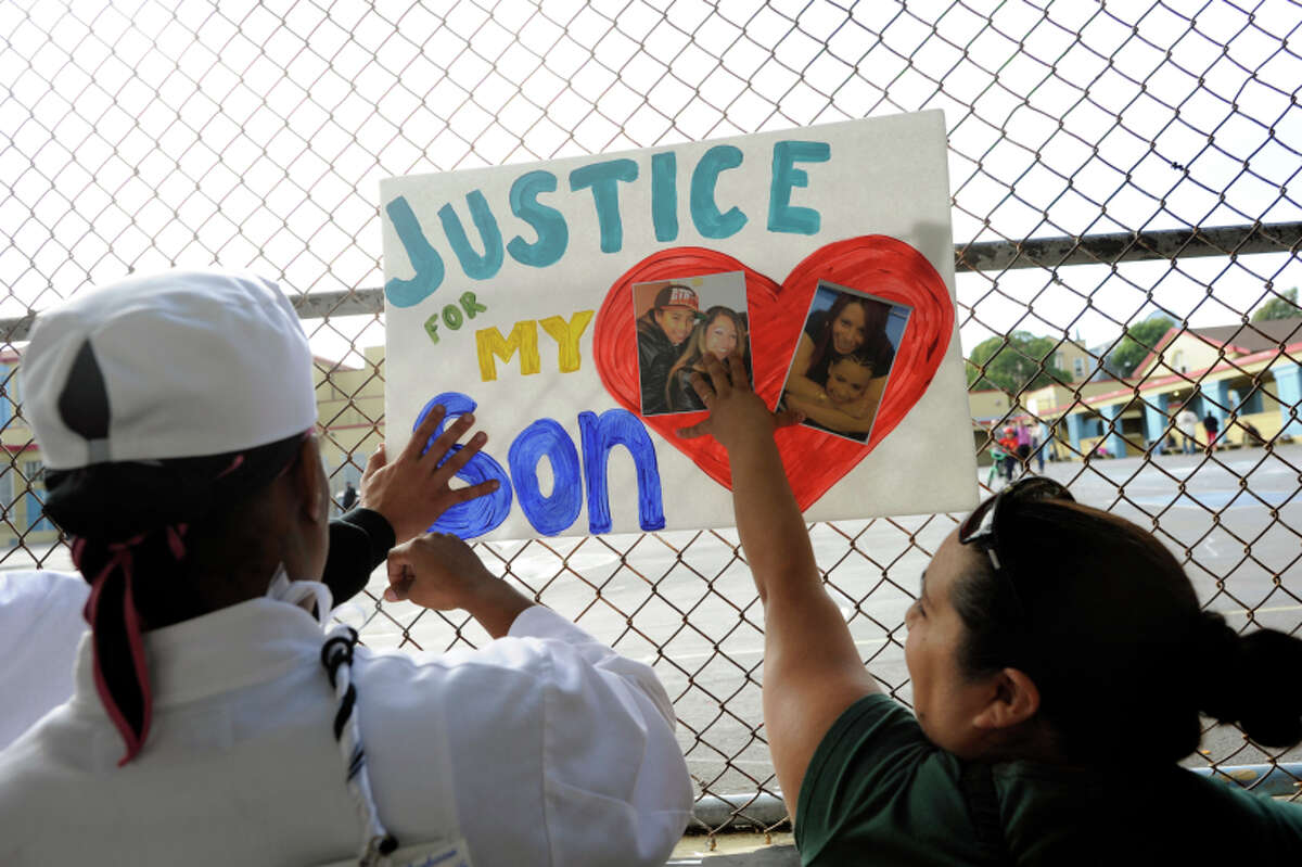 Rashawn's aunt Karolyn Green (left) and family friend Marisela Aceves place signs near where he was killed.