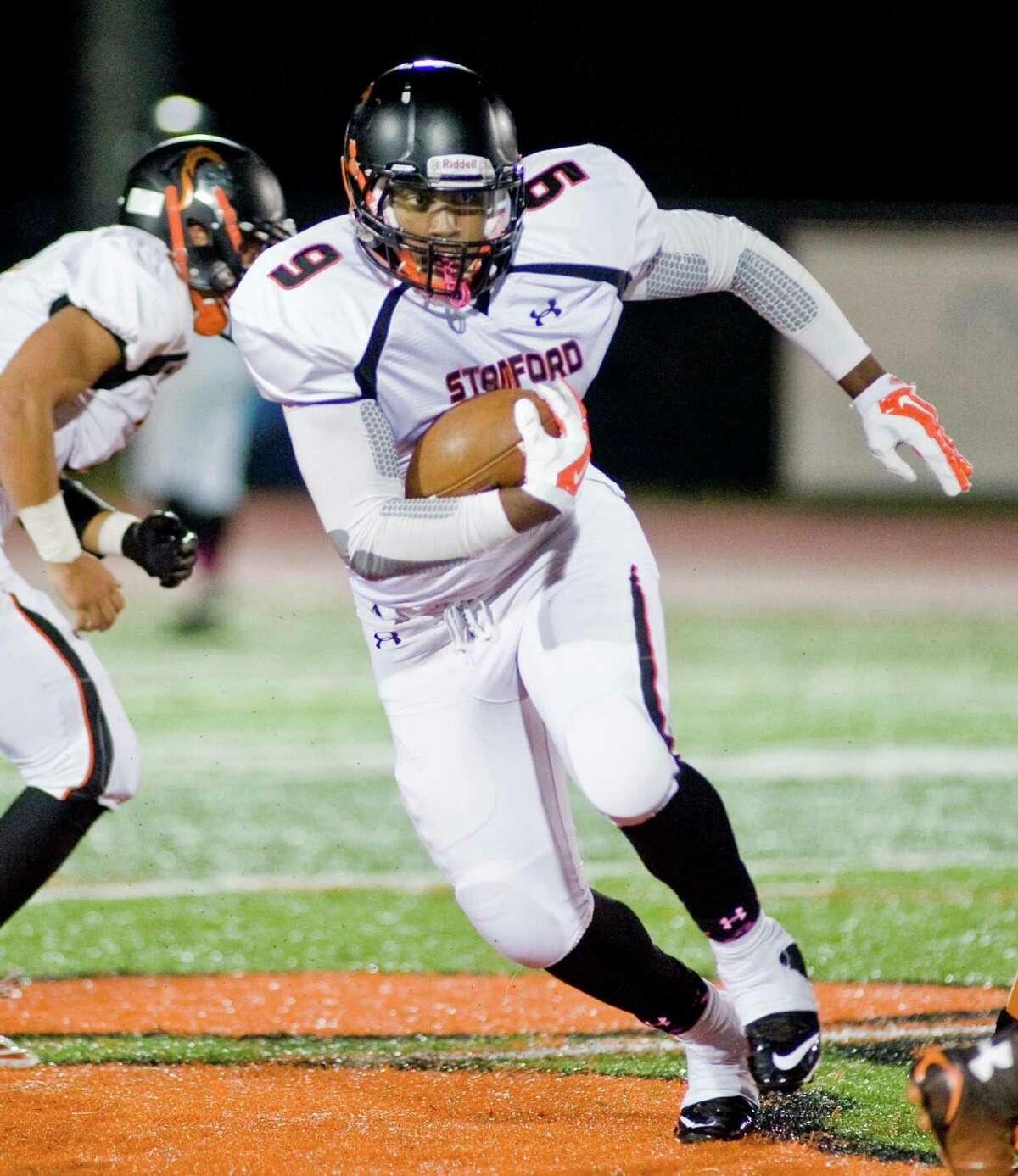 Stamford High School's Tyrell Diaz finds a hole in the Ridgefield High School line during a game at Ridgefield. Oct. 10, 2014