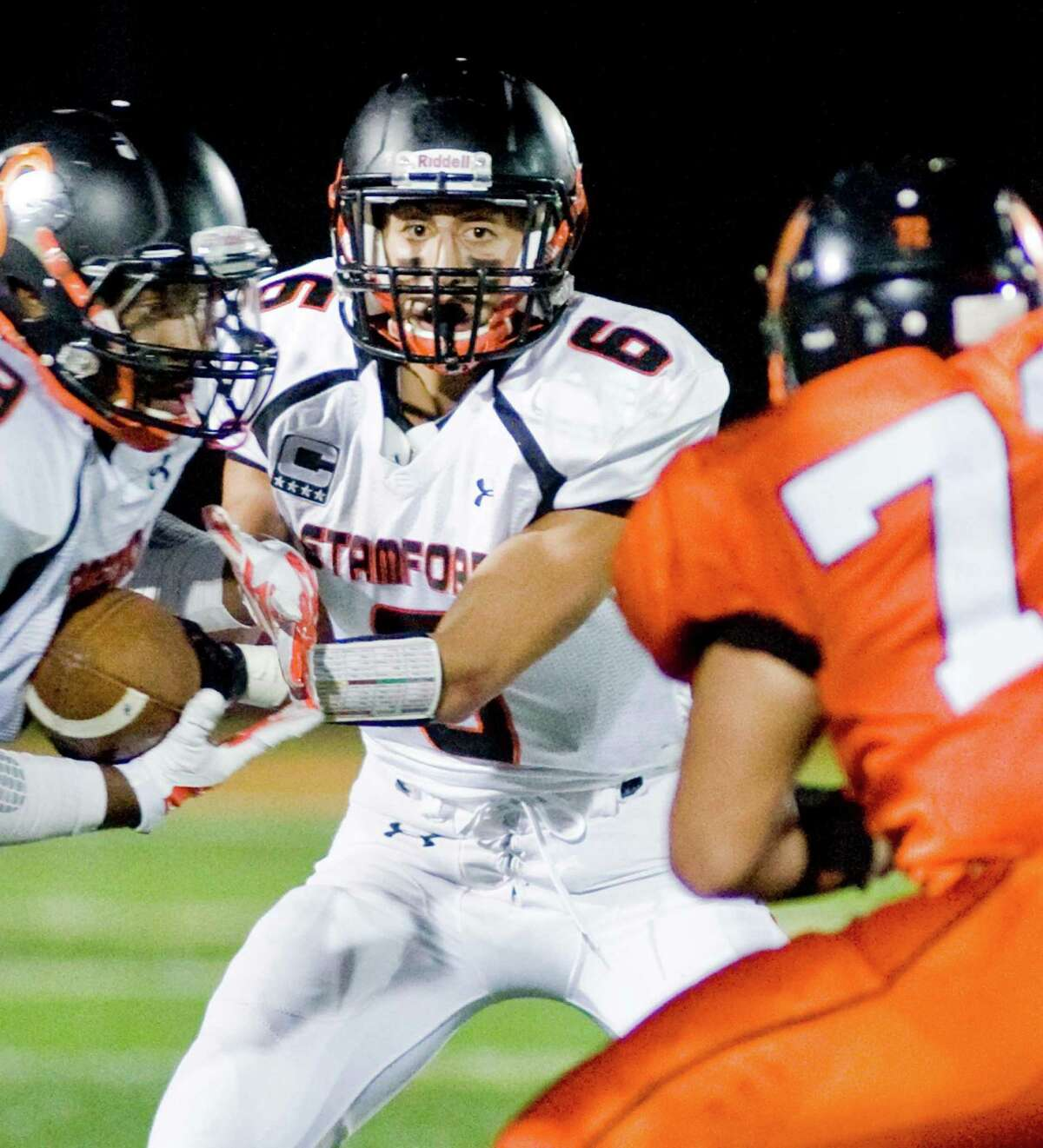 Stamford High School quarterback Tyler Serrichio hands off the ball in a game against Ridgefield High School, played at Ridgefield. Oct. 10, 2014