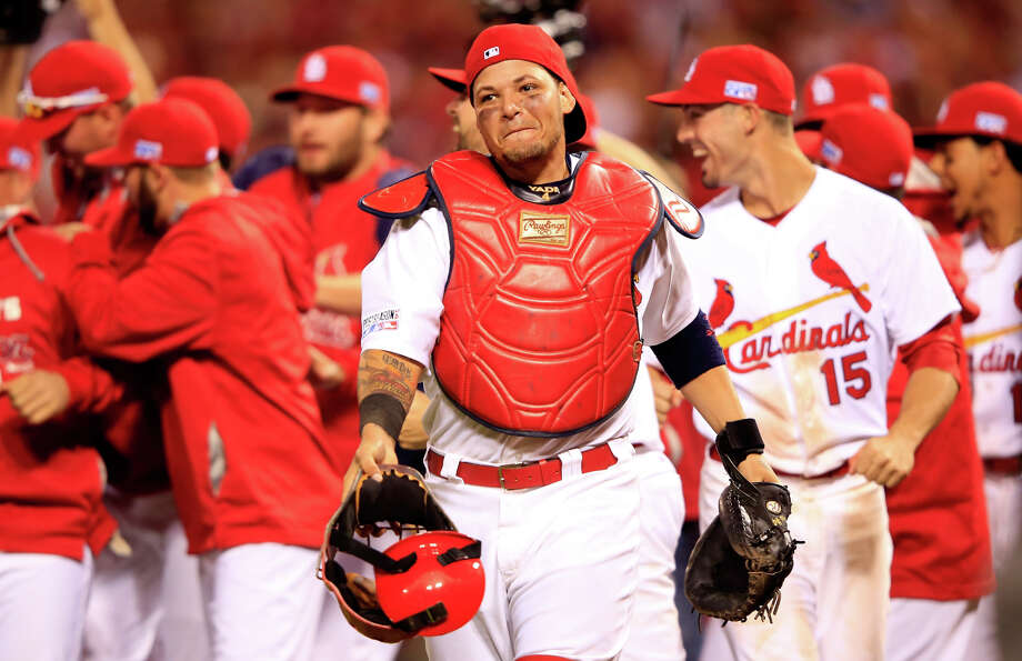 The Cardinals' Yadier Molina (center) has won the NL catching Gold Glove for the past six years and, like the Giants' Buster Posey, has played for two World Series winners. Photo: Jamie Squire / Getty Images / 2014 Getty Images
