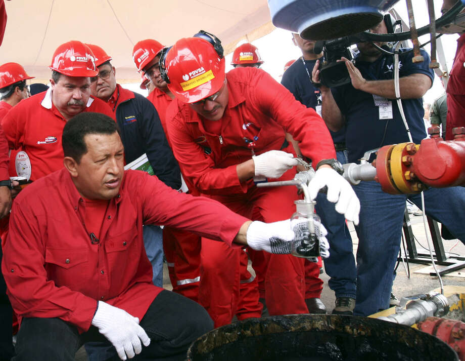 The late President Hugo Chavez of Venezuela examines a sample of crude oil at a nationalized oil field. The Houston oil company ConocoPhillips recently won a $2 billion arbitration award for compensation for assets seized in the South American nation Photo: PRESIDENCIA, Handout / PRESIDENCIA