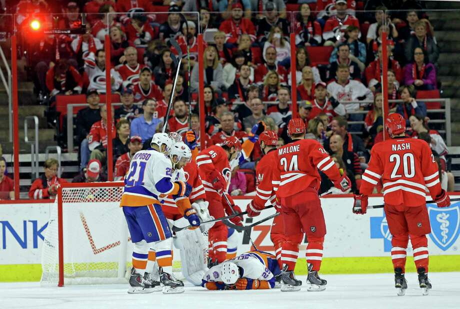 Teammates congratulate New York Islanders' Brock Nelson (29) as he falls to the ice after scoring against the Carolina Hurricanes during the second period of an NHL hockey game in Raleigh, N.C., Friday, Oct. 10, 2014. New York won 5-3. (AP Photo/Gerry Broome) ORG XMIT: NCGB112 Photo: Gerry Broome / AP