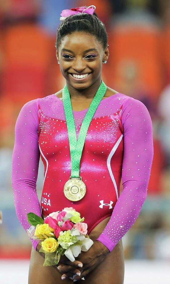 NANNING, CHINA - OCTOBER 10:  Gold medalist Simone Biles of United States celebrates during the medal ceremony after the Women's AllA!A©Around Final in day four of the 45th Artistic Gymnastics World Championships at Guangxi Sports Center Stadium on October 10, 2014 in Nanning, China.  (Photo by Lintao Zhang/Getty Images) ORG XMIT: 515667837 Photo: Lintao Zhang / 2014 Getty Images