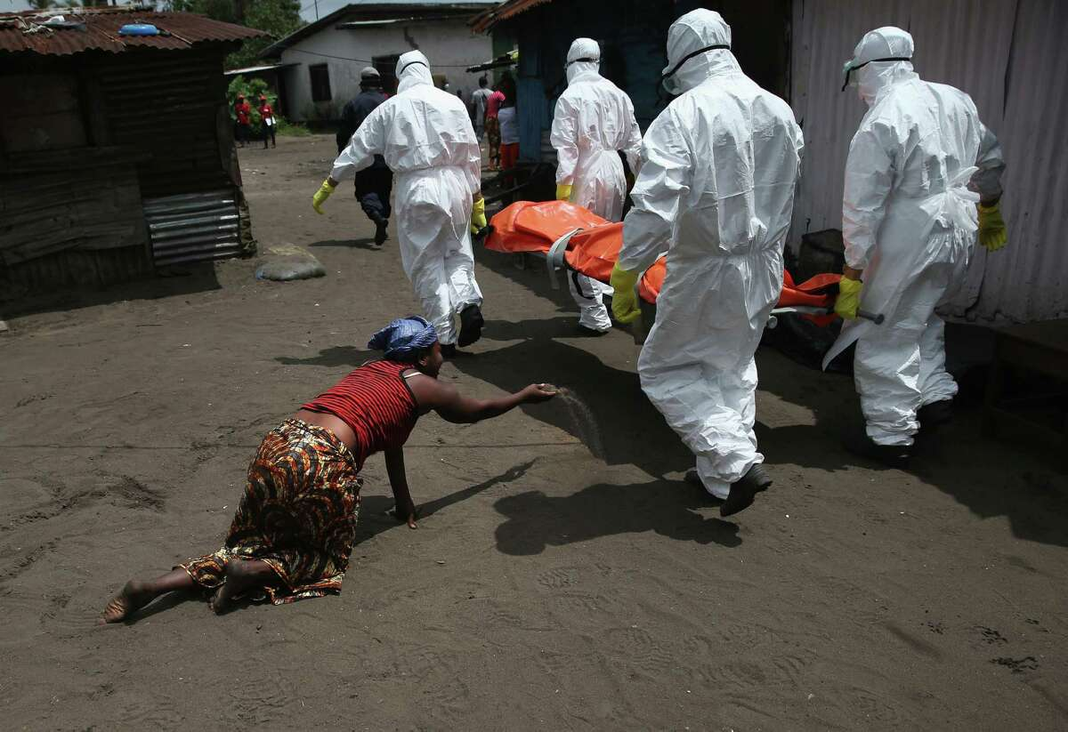 Updated caption:A woman throws a handful of soil towards the body of her sister Mekie Nagbe, 28, a market vendor, as Ebola burial team members take her for cremation on October 10, 2014 in Monrovia, Liberia. Mekie Nagbe had died outside her home earlier in the morning while trying to walk to a treatment center, according to her relatives. The burial of loved ones is important in Liberian culture, making the removal of infected bodies for cremation all the more traumatic for surviving family members. The World Health Organization says the Ebola epidemic has now killed more than 4,000 people in West Africa. (Photo by John Moore/Getty Images) ORG XMIT: 516330807