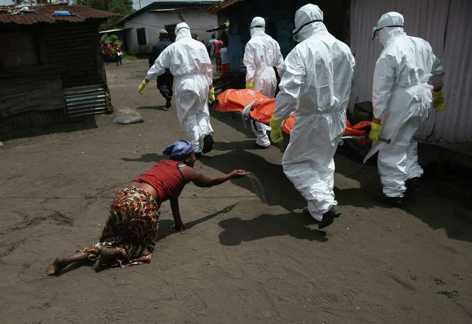 Updated caption:A woman throws a handful of soil towards the body of her sister Mekie Nagbe, 28, a market vendor, as Ebola burial team members take her for cremation on October 10, 2014 in Monrovia, Liberia. Mekie Nagbe had died outside her home earlier in the morning while trying to walk to a treatment center, according to her relatives. The burial of loved ones is important in Liberian culture, making the removal of infected bodies for cremation all the more traumatic for surviving family members. The World Health Organization says the Ebola epidemic has now killed more than 4,000 people in West Africa. (Photo by John Moore/Getty Images) ORG XMIT: 516330807 Photo: John Moore / 2014 Getty Images