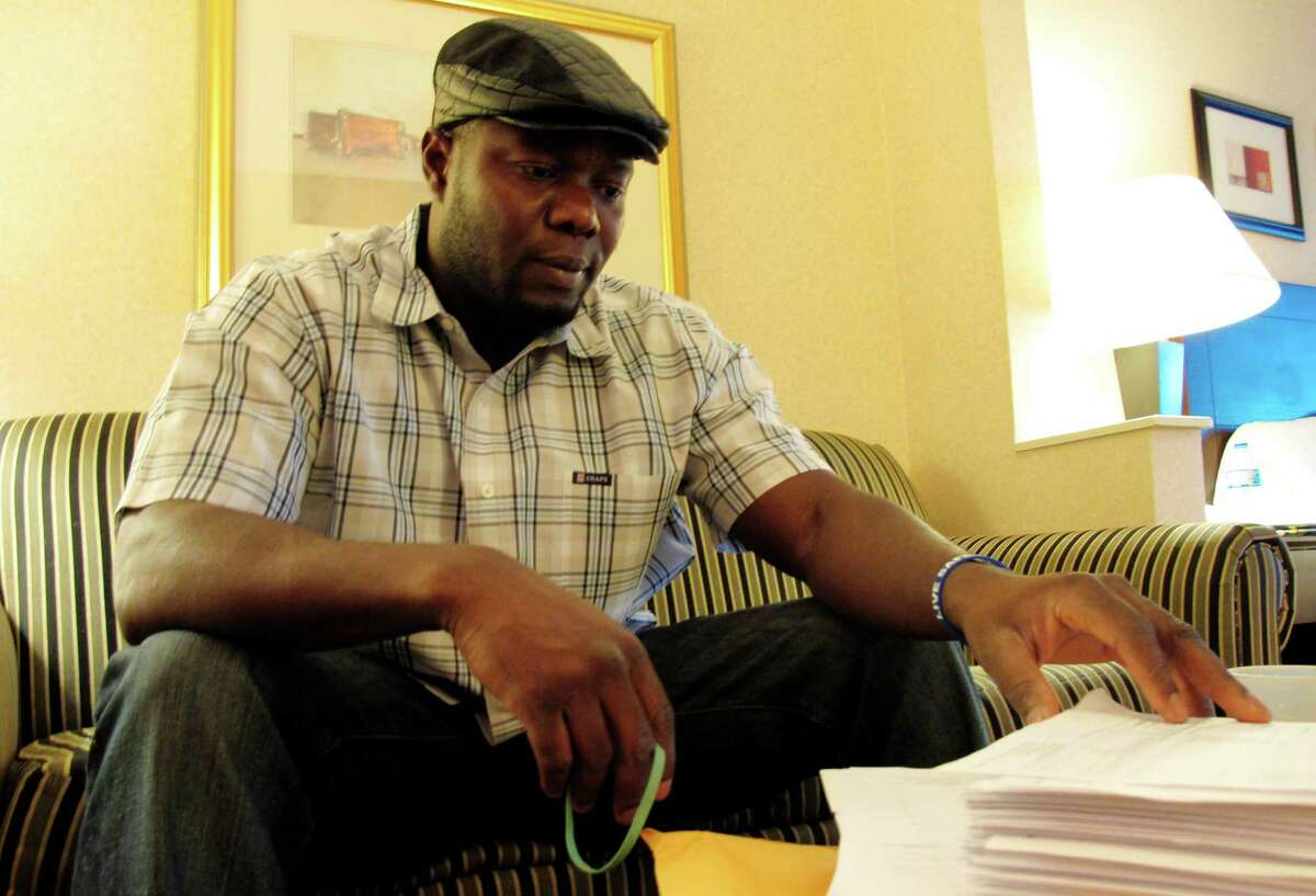 Josephus Weeks, nephew of ebola patient Thomas Eric Duncan who died earlier this week in Dallas, looks through hundreds of pages of medical documents in a hotel room Friday, Oct. 10, 2014, in Kannapolis, N.C. Duncan's temperature spiked to 103 degrees during the hours of his initial visit to an emergency room; a fever that was flagged with an exclamation point in the hospital's record-keeping system, his medical records show. (AP Photo/Allen G. Breed) ORG XMIT: NCAB101