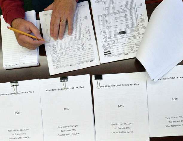 Media members look over 10 years of tax returns from Republican candidate for Attorney General John Cahill Friday morning Oct. 10, 2014, at the Republican State Committee offices in Albany, N.Y. (Skip Dickstein/Times Union) Photo: SKIP DICKSTEIN / 10028993A