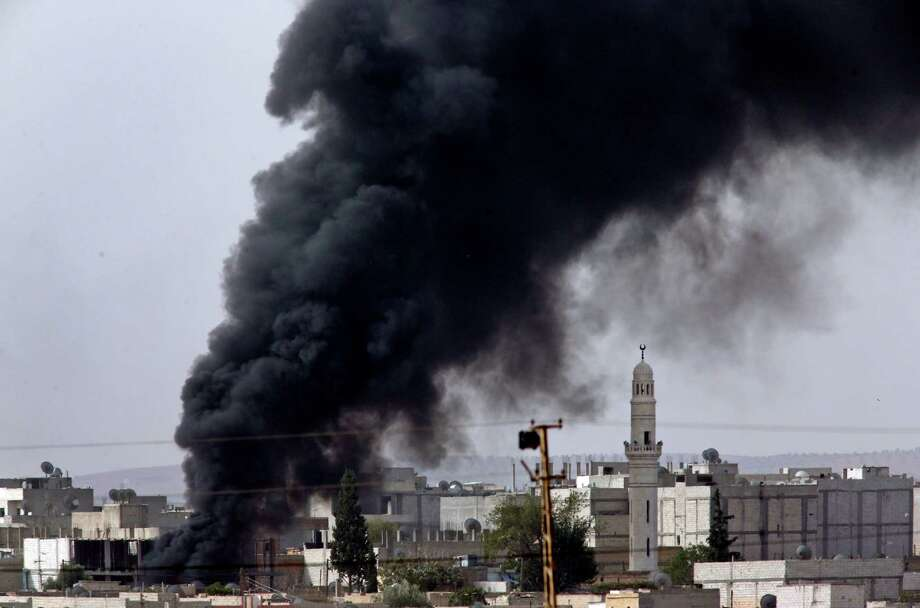 Heavy smoke from a fire caused by a strike rises in Kobani, Syria as fighting intensified between Syrian Kurds and the militants of Islamic State group, as seen from Mursitpinar in the outskirts of Suruc, at the Turkey-Syria border, Friday, Oct. 10, 2014. Kobani, also known as Ayn Arab, and its surrounding areas, has been under assault by extremists of the Islamic State group since mid-September and is being defended by Kurdish fighters. (AP Photo/Lefteris Pitarakis) ORG XMIT: AXLP101 Photo: Lefteris Pitarakis / AP