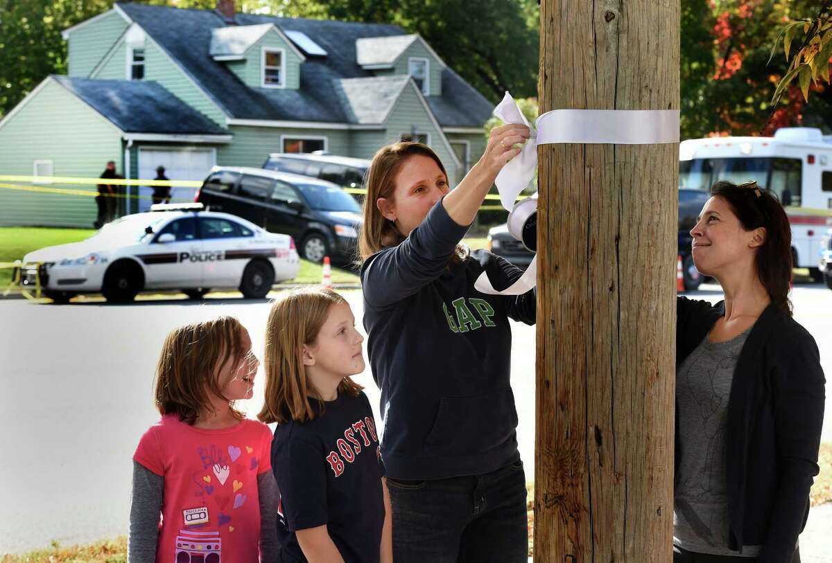 Laura Hammes ties a white ribbon to a pole across the street from the homicide scene Friday afternoon, Oct. 10, 2014 in Guilderland, N.Y. Hammes said that she was told that the color white was the sign of mourning in China. With Hammes are her daughter Maddie, 9, second from left, Olivia Rutherford, 9, left and Jennifer Rutherford, right. Both children go to Guilderland Elementary School which is where the deceased children attended school. (Skip Dickstein/Times Union)