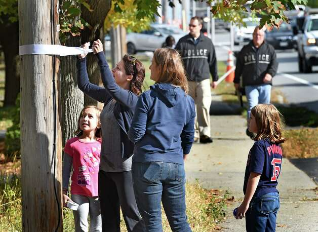 As State Police BCI investigators canvas the area Jennifer Rutherford ties a white ribbon to a pole across the street from the homicide scene  Friday afternoon, Oct. 10, 2014, in Guilderland, N.Y.  With Rutherford are her daughter Maddie, 9,  left, Olivia Rutherford, 9, right, and Laura Hammes, second from right.  Both children go to Guilderland Elementary School which is where the deceased attended school.   (Skip Dickstein/Times Union) Photo: SKIP DICKSTEIN