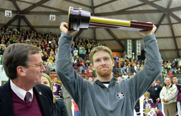 Last year's hockey team captain Mat Bodie holds the NCAA trophy and Union College president Stephen Ainlay, left, looks on as Union celebrates their NCAA win before the start of their season opener against American International at Messa Rink Friday Oct. 10, 2014, in Schenectady, NY.  (John Carl D'Annibale / Times Union) Photo: John Carl D'Annibale / 10028936A