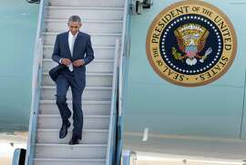 President Barack Obama walks to the tarmac after arriving at San Francisco International Airport on Air Force One on Friday, Oct. 10, 2014, in San Francisco.